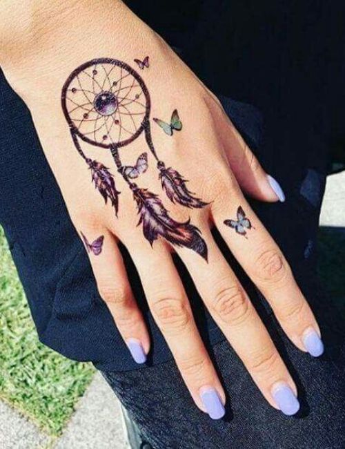 dream catcher tattoo with small butterflies on back hand